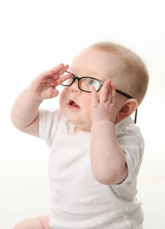 Portrait of a baby wearing eyeglasses and playing with them Stock Photo
