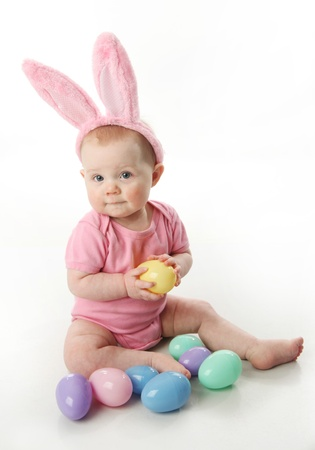 Portrait of a cute baby dressed in Easter bunny ears with a basket full of eggs photo