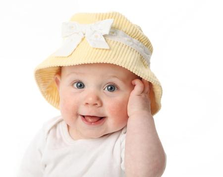 白い背景で隔離された黄色い帽子をかぶっている舌を示している笑顔の赤ちゃん女の子