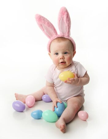 kids costume: Portrait of a cute baby dressed in Easter bunny ears with pastel eggs