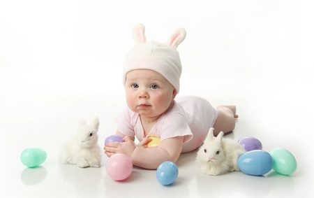 hand baskets: Portrait of a cute baby dressed in Easter bunny ears with pastel eggs