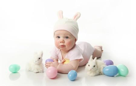 bunny ears: Retrato de un lindo beb� vestido con orejas de conejo de Pascua con huevos al pastel Foto de archivo