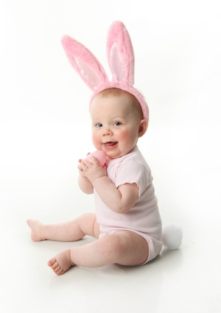 kids costume: Portrait of a cute baby dressed in Easter bunny ears pastel eggs Stock Photo
