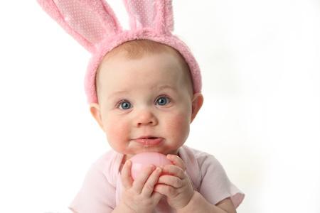 bunny ears: Retrato de un lindo beb� vestido con las orejas del conejito de pascua huevos de colores pastel Foto de archivo