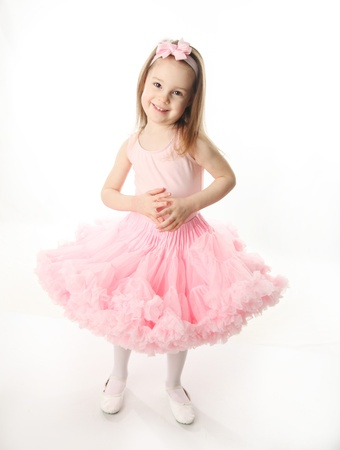 Portrait of an adorable preschool age girl playing dress up wearing a ballet tutu, isolated on white photo
