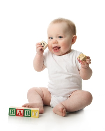 Portrait of a cute baby sitting playing with wooden blocks  Imagens
