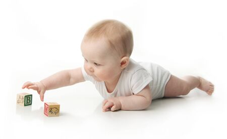 reflexes: Portrait of a cute baby sitting playing with wooden blocks  Stock Photo