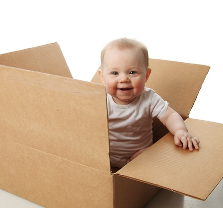 Portrait of a cute baby sitting in a brown cardboard box photo