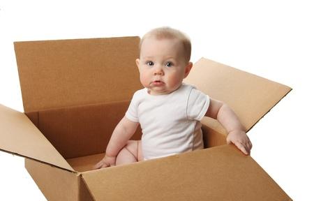 storage box: Portrait of a cute baby sitting in a brown cardboard box