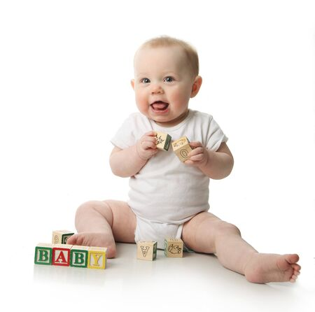 babysitter: Portrait of a cute baby sitting playing with wooden blocks  Stock Photo