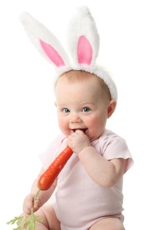 lapin blanc: Portrait d'un joli b�b� v�tu d'oreilles de lapin de P�ques avec une carotte