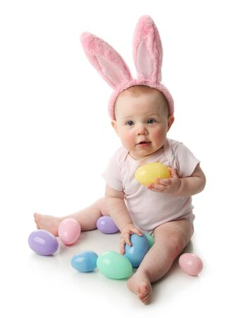 Portrait of a cute baby dressed in Easter bunny ears with pastel eggs photo