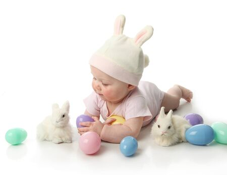 Portrait of a cute baby dressed in Easter bunny ears with eggs