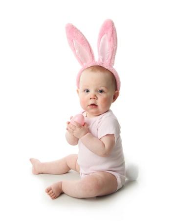 Retrato de un lindo bebé vestido con las orejas del conejito de pascua huevos de colores pastel Foto de archivo - 9939529