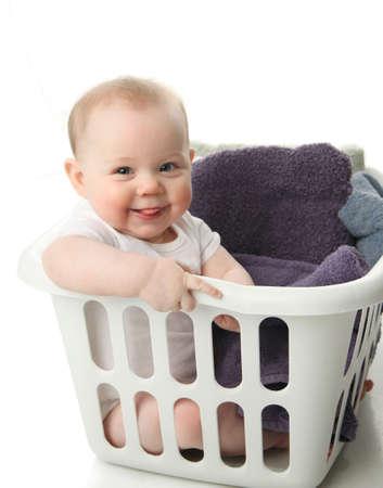 lavanderia: Retrato de un adorable beb� sentado en un cesto de la ropa con toallas
