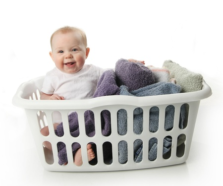 warm cloth: Portrait of an adorable baby sitting in a laundry basket with towels