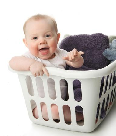 bebe sentado: Retrato de un adorable beb� sentado en una canasta de lavander�a con toallas Foto de archivo