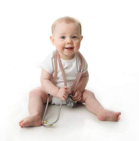 Adorable baby sitting up wearing and playing with a medical stethoscope, isolated on white photo
