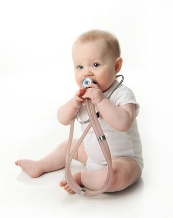 Adorable baby sitting up wearing and playing with a medical stethoscope, isolated on white Stockfoto