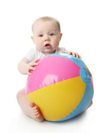 Adorable bebé jugando con una pelota de playa colorida, aislada en blanco