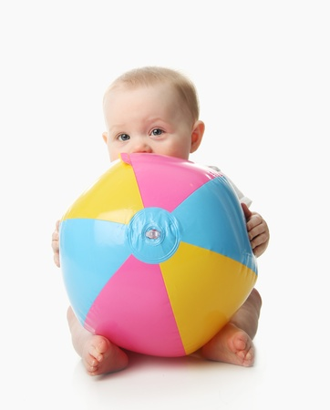 babies: Adorable baby playing with a colorful beach ball, isolated on white Stock Photo