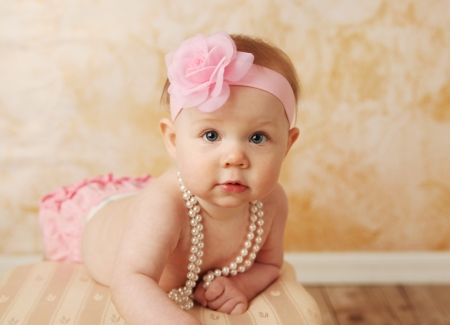 fashion jewelry: Adorable young baby girl wearing a vintage pearl necklace and pink rose headband Stock Photo