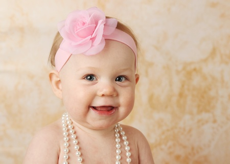 Adorable young baby girl wearing a vintage pearl necklace and pink rose headband photo