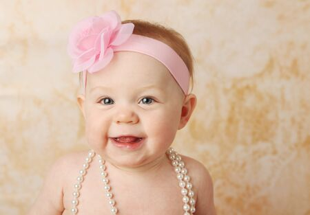 Adorable young baby girl wearing a vintage pearl necklace and pink rose headband Stock Photo