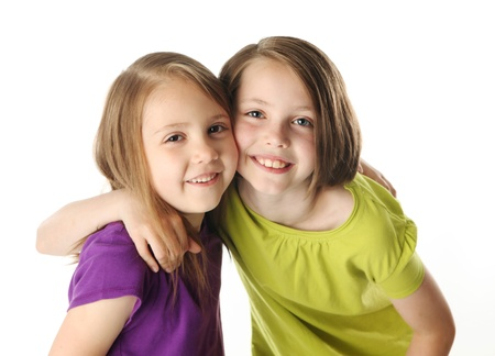 Cute young sisters isolated on white in studio