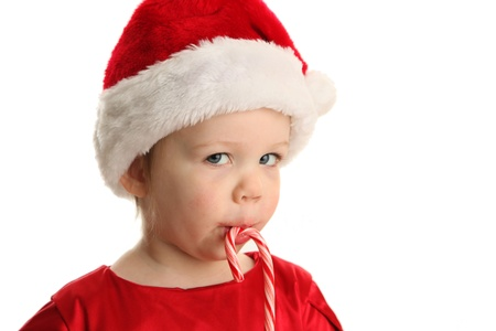 Christmas Portrait of a beautiful little child girl wearing a santa hat and holding a candy cane