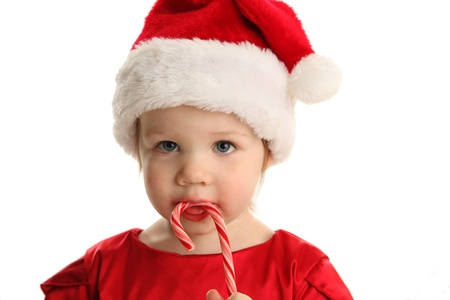 Christmas Portrait of a beautiful little child girl wearing a santa hat and holding a candy cane photo