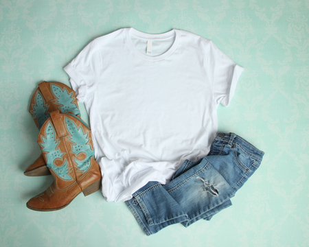 Flat Lay mockup of white t shirt on aqua background with cowboy boots and ripped jeans