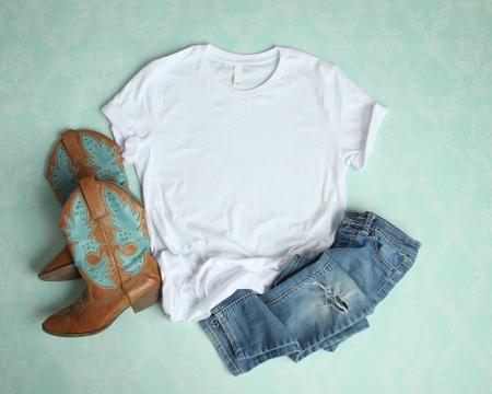 Flat Lay Modell des weißen T-Shirts auf Aquahintergrund mit Cowboystiefeln und zerrissenen Jeans Standard-Bild