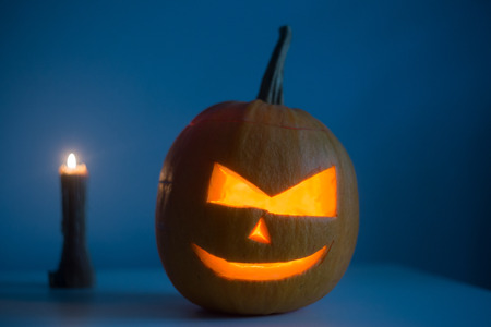 Scary Halloween pumpkin with eyes glowing inside at dark blue background. Copy space text.