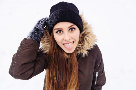 warmly: Happy woman warmly clothed in a cold winter snow forest shows tongue at camera. Copy space text. Stock Photo