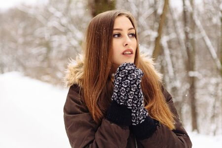 space text: Woman warmly clothed in a cold winter snow forest with trees on background. Copy space text.