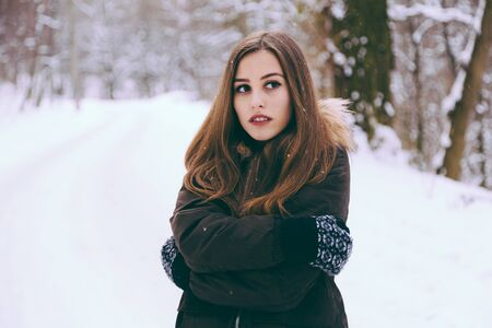 warmly: Woman warmly clothed in a cold winter snow forest with trees on background. Copy space text.