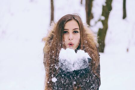 warmly: Woman warmly clothed in a cold winter forest blows snow out. Copy space text. Stock Photo