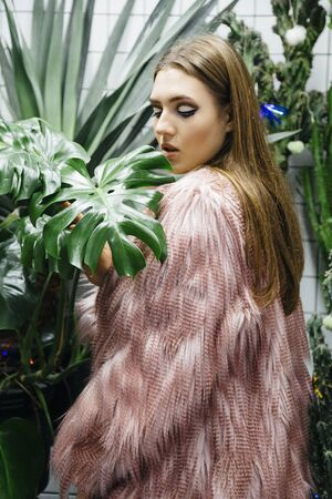 Beautiful young woman with large green leafs in faux eco fur coat over white checkered background. Natural organic vegan concept.