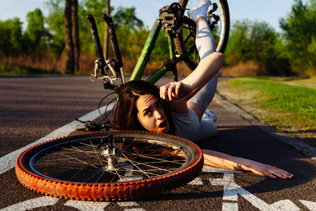 emergency braking: Girl fell from bicycle in park. Accident dangerous bike ride on the asphalt. Safe driving concept. Stock Photo