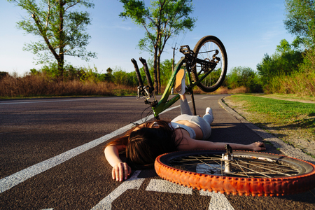 Girl fell from bicycle in park. Accident dangerous bike ride on the asphalt. Safe driving concept. Stock Photo