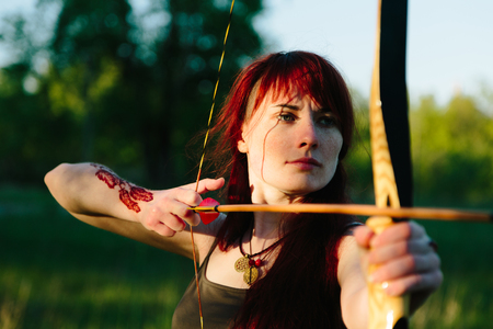 Female ginger hair archer shooting targets with her bow and arrow. Concentration, target, success concept. Copy space text. Stock Photo