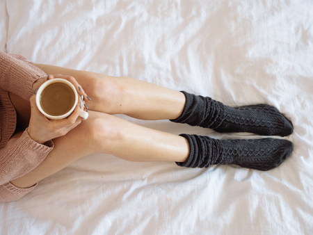Portrait of woman on the bed with phone and cup of coffee in hands. Top view. Cozy morning. Stock Photo