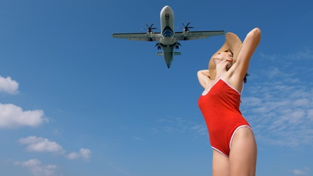 Tourist woman in red swimsuit and hat welcomes airplane for travel. Hello vacation concept.