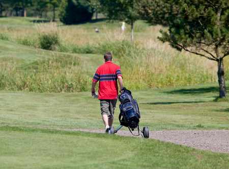 golfer walking down the fairway photo