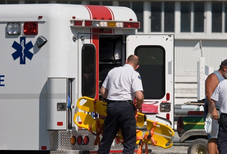 Paramedic unloading back board at accident