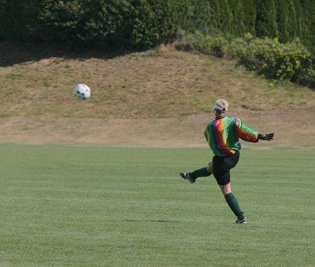 ゴールキーパー レディース娯楽リーグでサッカー ボールを蹴る 写真素材