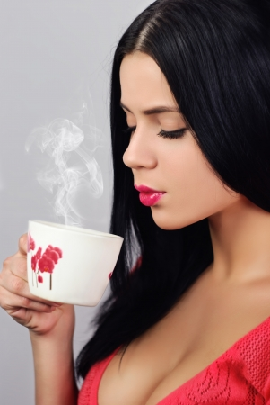 studio portrait Young the woman, drinking hot drink