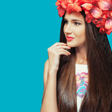 Photo of a beautiful girl on a blue background, head woven red flowers photo