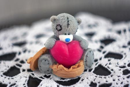 Toy gray teddy bear sitting holding a big heart.